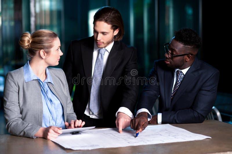 Empregador que explica o plano de negócios a seus colegas imagens de stock royalty free