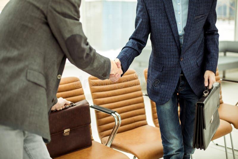 Empregados da empresa com as pastas que agitam as mãos na entrada de um escritório moderno imagens de stock