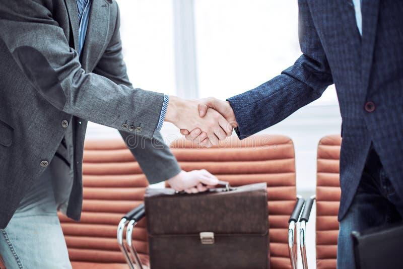 Empregados da empresa com as pastas que agitam as mãos na entrada de um escritório moderno imagem de stock
