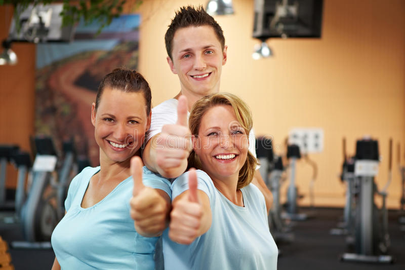Empregados da ginástica que mantêm os polegares foto de stock royalty free