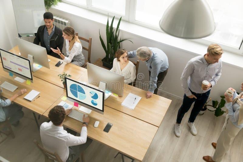Empregados de escritório que trabalham junto compartilhando da mesa usando computadores mim fotos de stock
