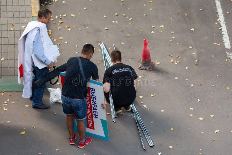 Empregados de uma agência de propaganda com elementos do projeto da propaganda exterior para a campanha eleitoral do prefeito de  fotografia de stock royalty free