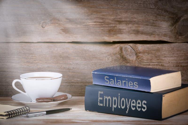 Empregados e salários Pilha de livros na mesa de madeira imagem de stock royalty free