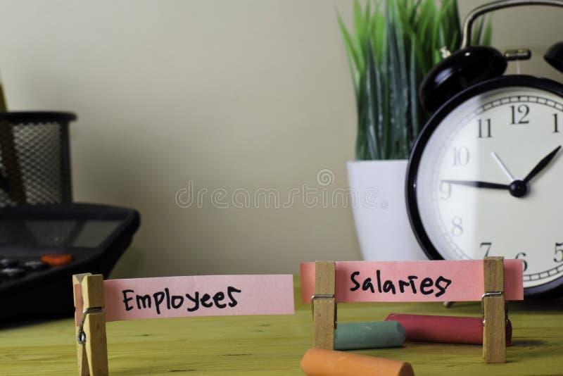 Empregados e sal?rios Escrita em notas pegajosas em Pegs de roupa na mesa de escritório de madeira foto de stock