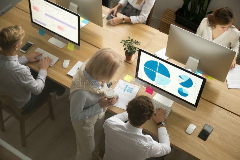 Empregados incorporados que trabalham em computadores no escritório junto, parte superior imagem de stock