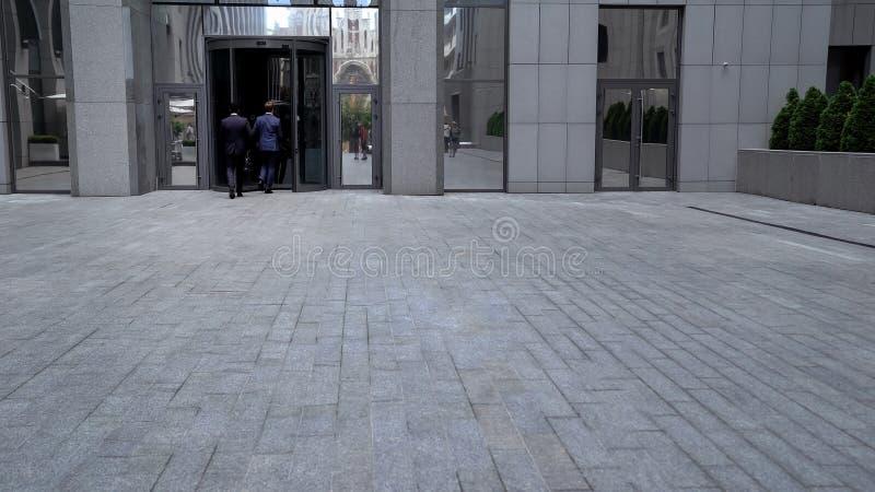 Empregados que entram em sócios de visita do centro de negócios na tempo-gestão do escritório foto de stock