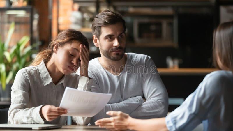Empregados que sentam-se no café que acusa o erro do colega no relatório financeiro imagens de stock