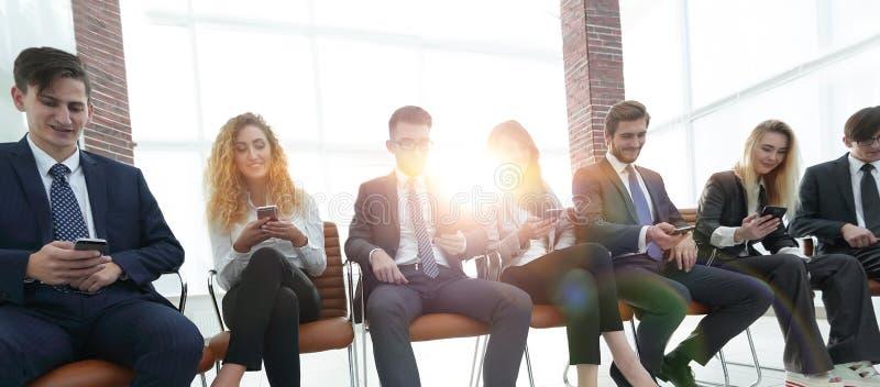 Empregados que usam smartphones no escritório fotografia de stock