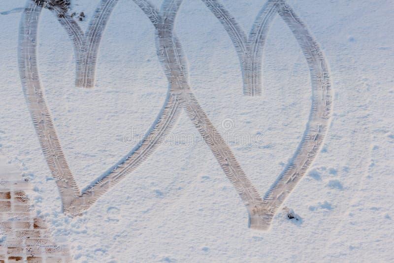 Empreinte de deux coeurs dessinés dans la neige images stock