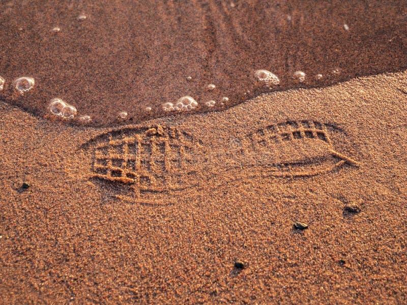 Empreinte de pas d'une chaussure sur une plage avec de l'eau photo stock
