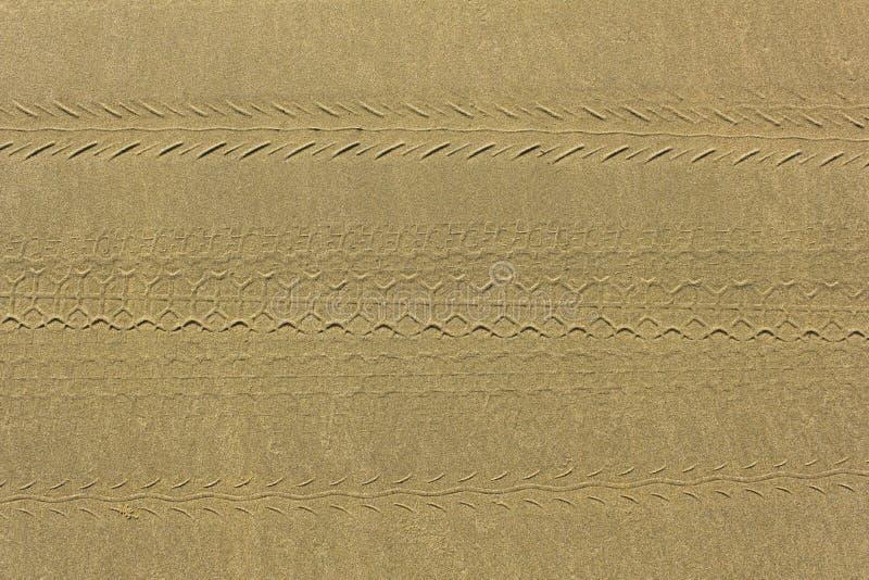 Empreintes de divers pneus de moto sur la vue supérieure à sable jaune grise texture ext?rieure naturelle photos libres de droits