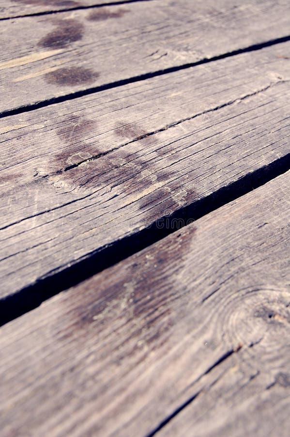 Empreintes de pas après les pieds humides sur le passage couvert/plancher en bois photos libres de droits