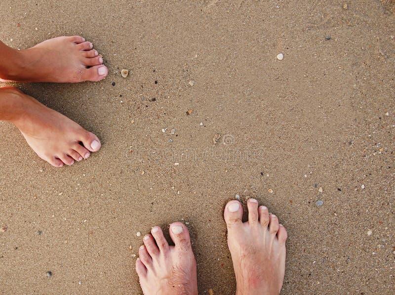 Empreintes de pas d'un couple affectueux dans le sable sur le bord de la mer image stock