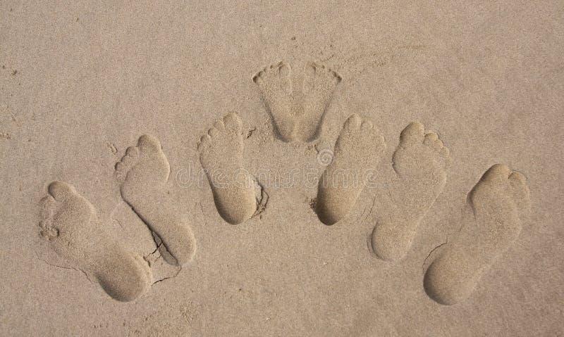 Empreintes de pas d'un famille dans le sable sur la plage photo libre de droits