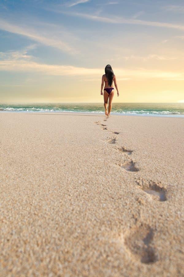 Empreintes de pas d'une femme sur la plage image libre de droits