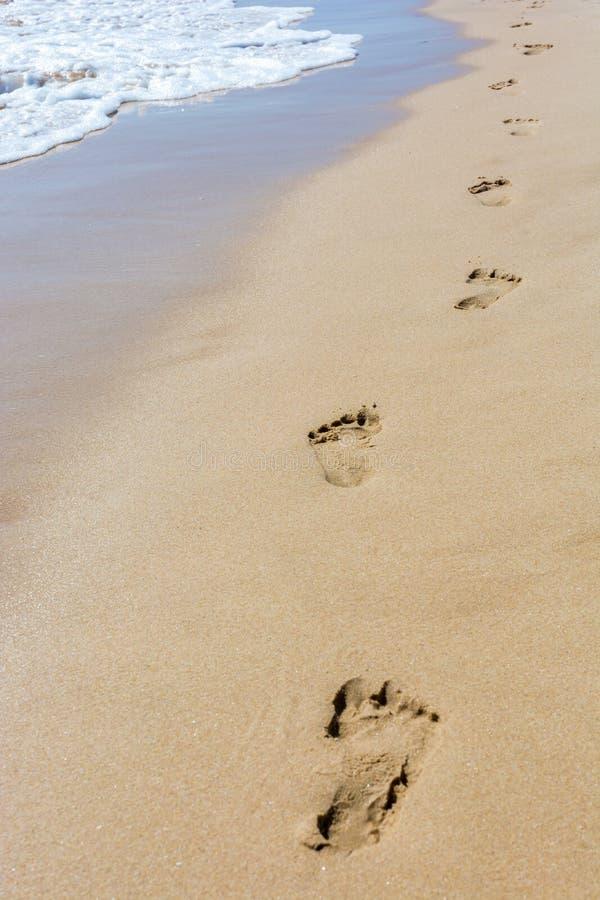 Empreintes de pas dans le sable d'une plage images libres de droits