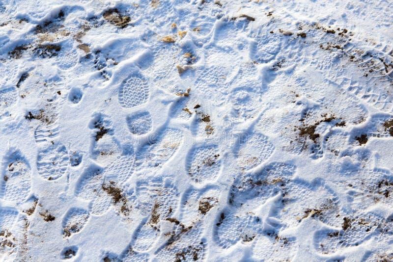Empreintes de pas des chaussures sur la neige comme fond images stock