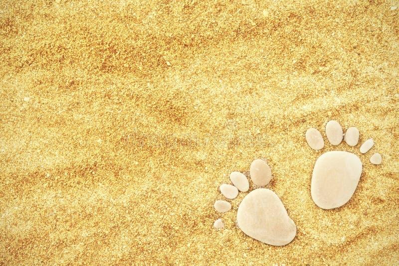 Empreintes de pas des pierres sur à sable jaune sur la plage en été photo stock