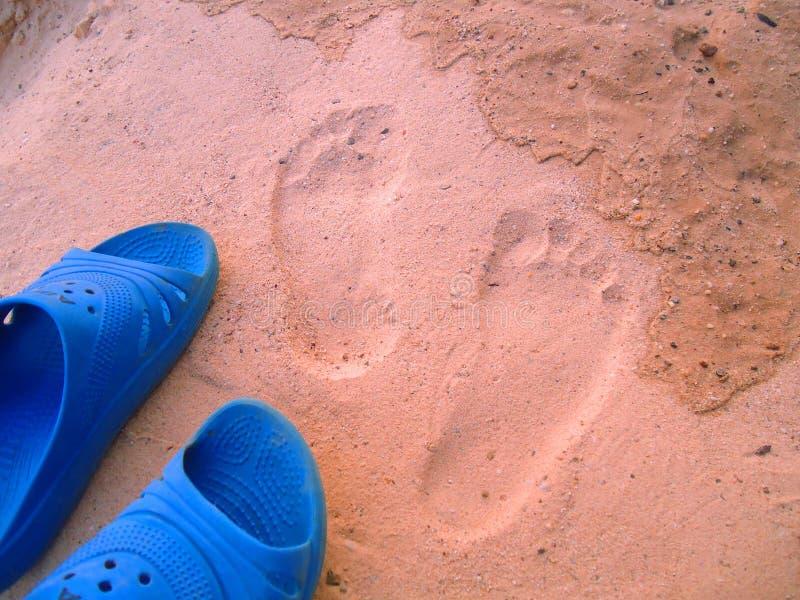 Empreintes de pas et chaussures sur le sable images libres de droits