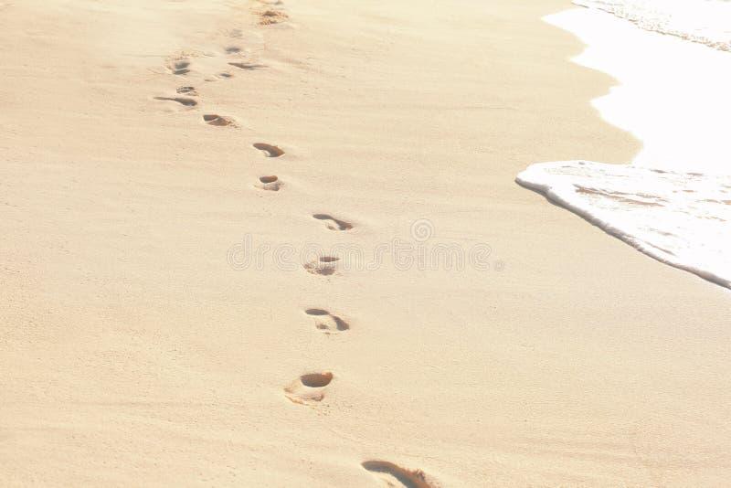 Empreintes de pas humaines sur le sable de plage photographie stock