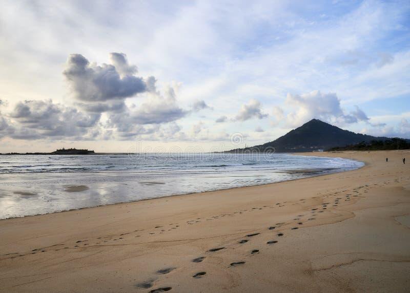 Empreintes de pas sur la plage à la colline photo stock
