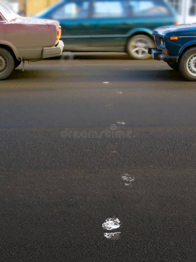 Empreintes de pas sur la route photographie stock