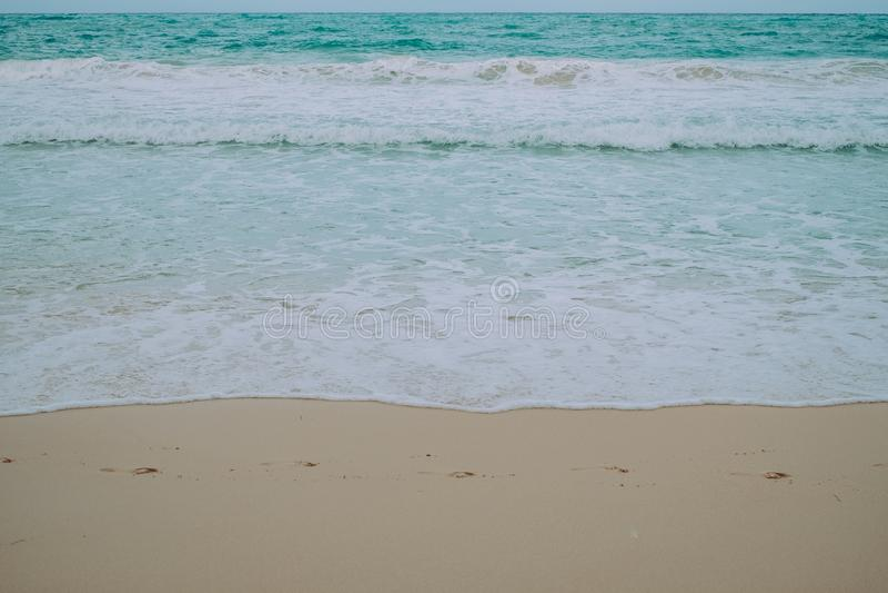 Empreintes de pas sur le sable, les vagues de mer et la mousse fins dans la plage image libre de droits