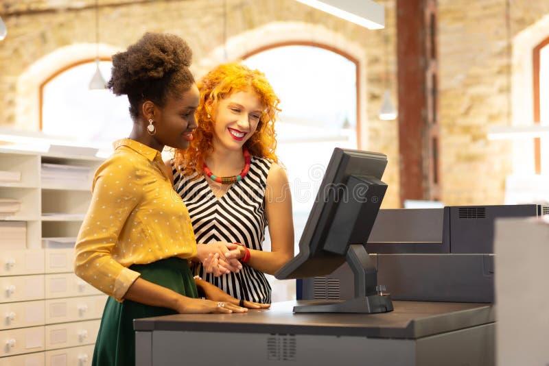 Empresária ensinando funcionário a usar o sistema de caixa foto de stock royalty free