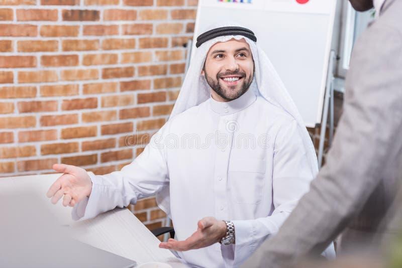 Empresário árabe sorrindo e gestando imagem de stock royalty free