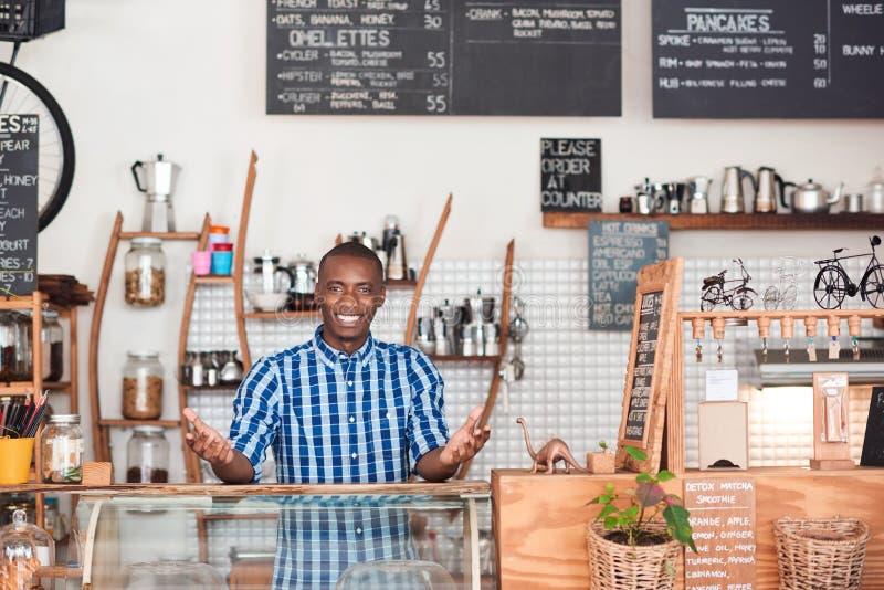 Empresário africano amigável que está atrás do contador de seu café fotografia de stock royalty free