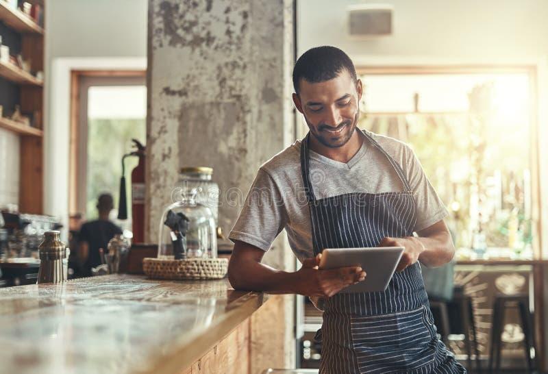 Empresário africano novo que usa a tabuleta digital em seu café imagens de stock