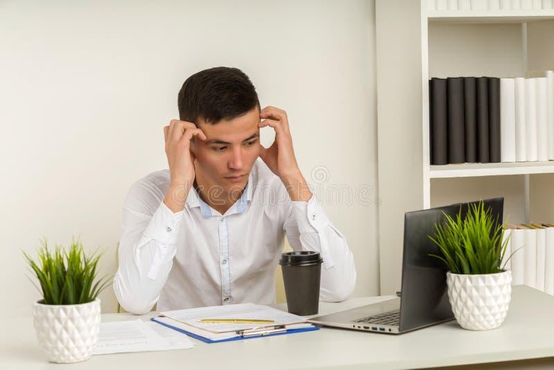 Empresário asiático gravemente frustrado que sofre de enxaqueca no local de trabalho, sentindo-se cansado foto de stock royalty free