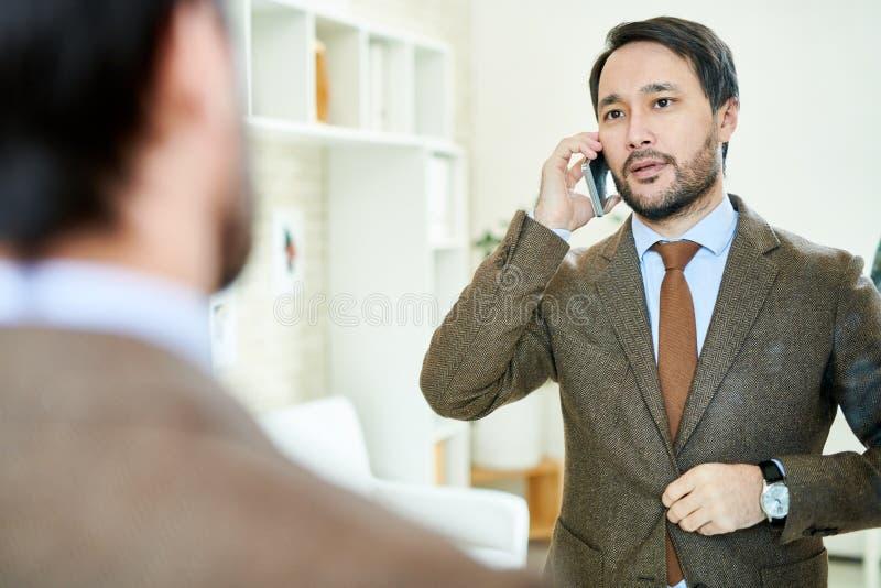 Empresário bem sucedido que fala no telefone imagens de stock royalty free