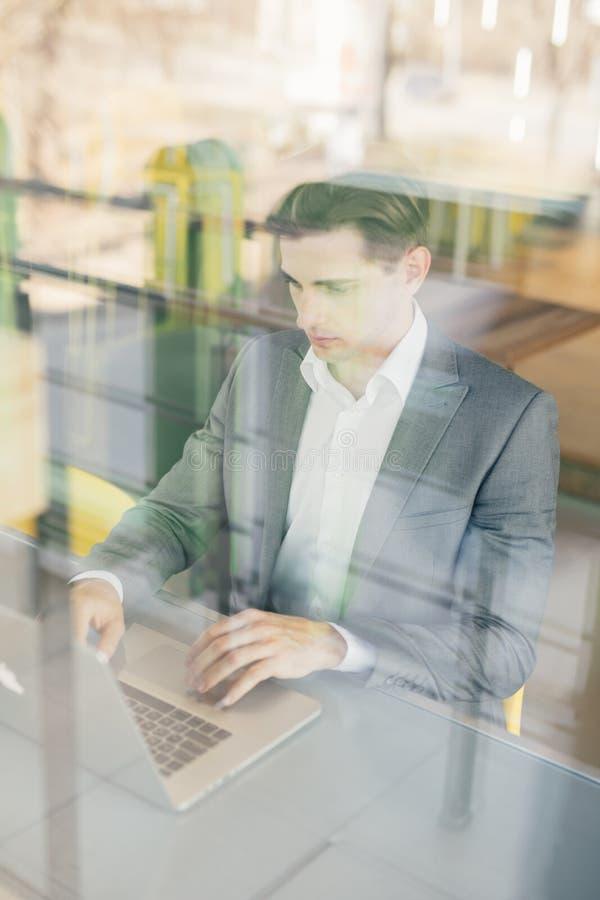 Empresário bem sucedido que sorri na satisfação como verifica a informação em seu laptop ao trabalhar em um escritório domiciliár imagens de stock