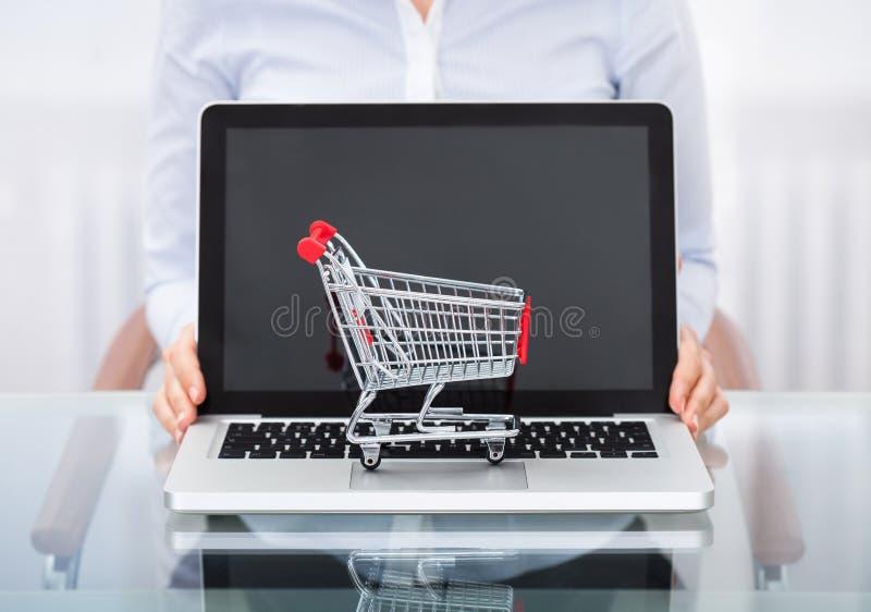 Empresário com carrinho de compras e portátil imagens de stock