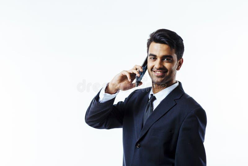Empresário considerável que fala no telefone, sorriso do homem de negócios, olhando a câmera imagens de stock royalty free