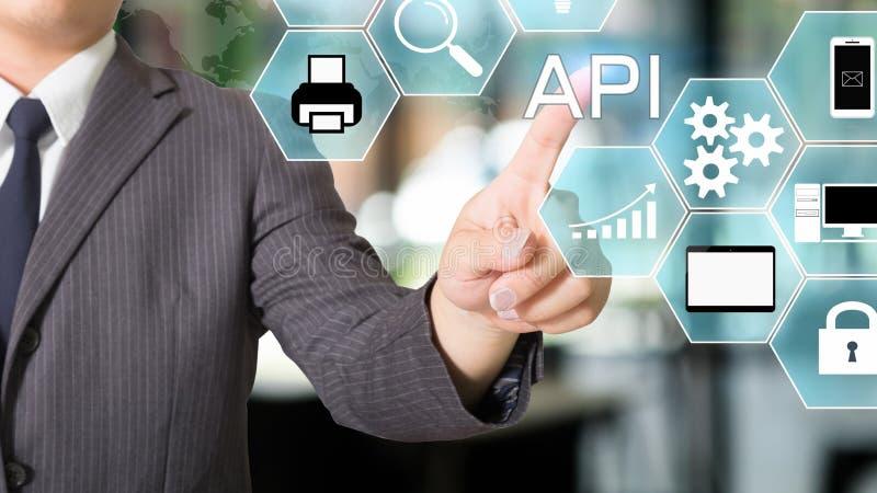 Empresário da Interface de Programação de Aplicações de API apontando um ícone visual fotografia de stock