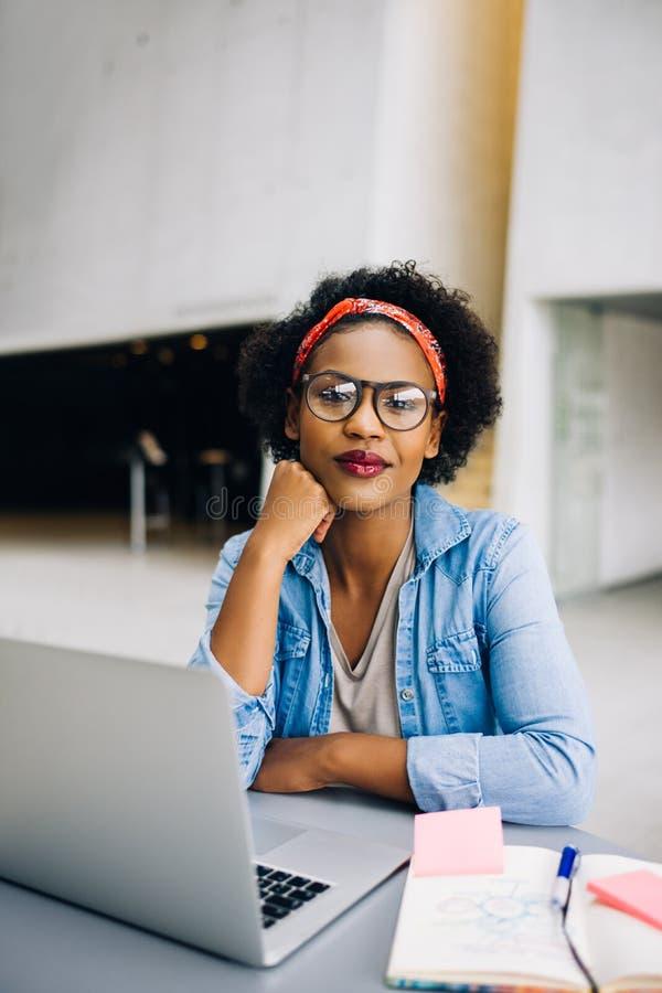 Empresário fêmea africano novo de sorriso que trabalha em seu negócio fotografia de stock royalty free