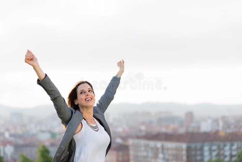 Empresário fêmea bem sucedido que aumenta os braços fotografia de stock