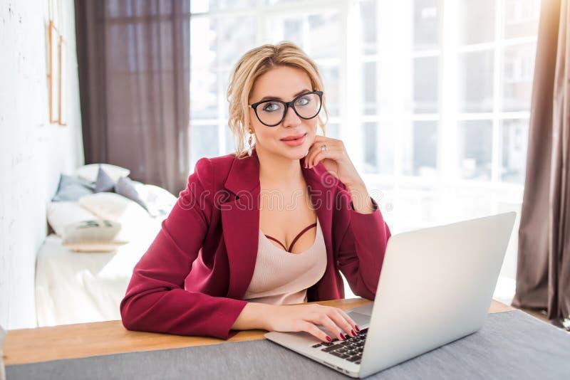 Empresário fêmea novo que senta-se na tabela em seu escritório domiciliário que trabalha no portátil imagens de stock royalty free
