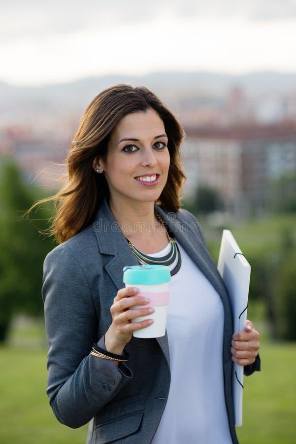 Empresário fêmea novo que toma uma ruptura de café imagem de stock