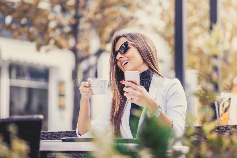 Empresário feliz que trabalha com um telefone, um portátil e um caf bebendo imagem de stock