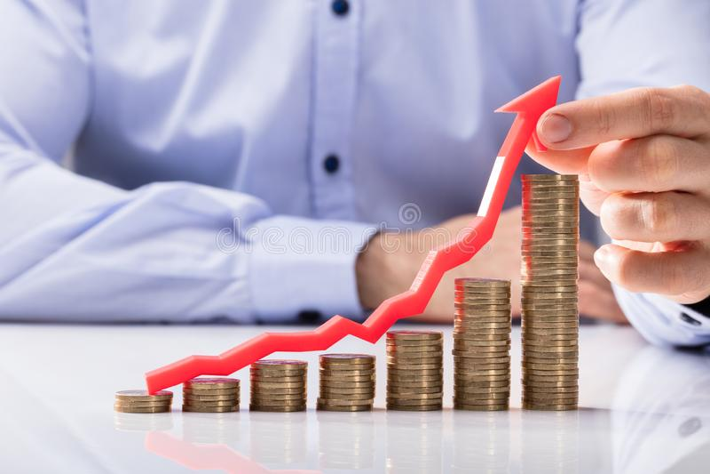 Empresário Holding Arrow Over que aumenta moedas empilhadas foto de stock royalty free