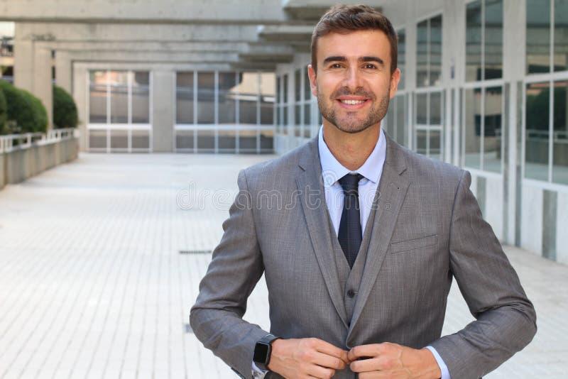 Empresário lindo que abotoa-se acima de seu terno costurado fotografia de stock