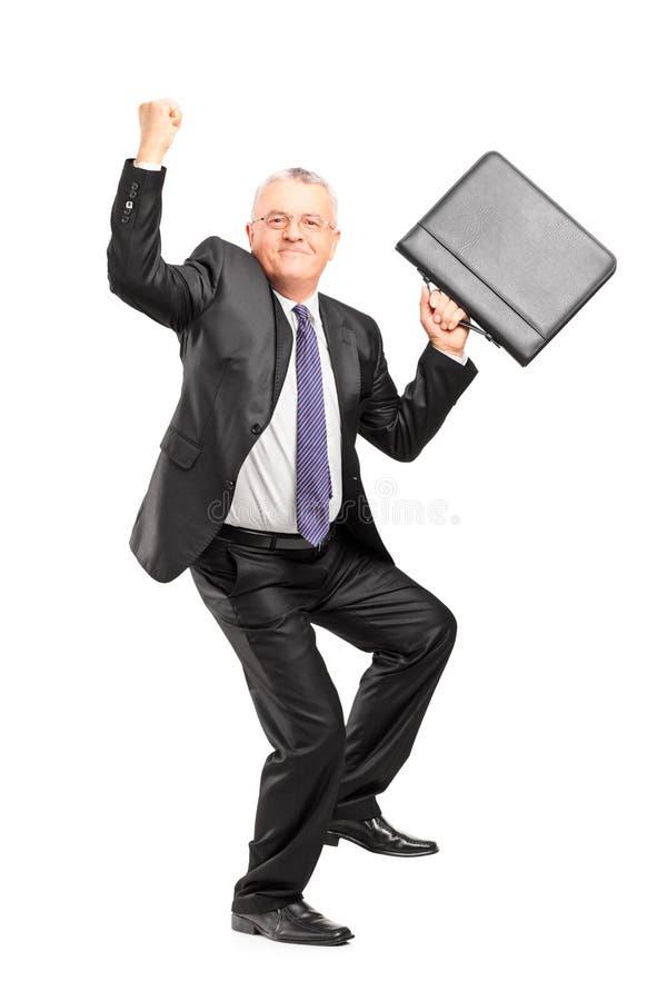 Empresário maduro feliz com mãos e a pasta levantadas imagem de stock