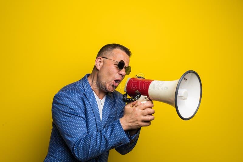 Empresário maduro nos óculos de sol que falam com o altifalante isolado no fundo amarelo imagem de stock