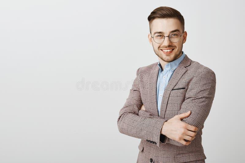 Empresário masculino europeu bonito esperto e inteligente ambicioso nos vidros e nas mãos à moda do cruzamento do revestimento so imagens de stock
