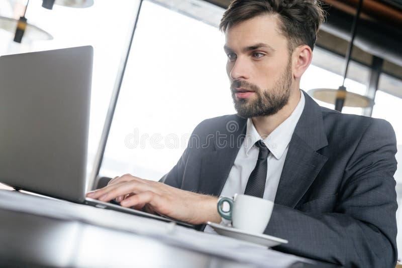 Empresário no almoço de negócio no café bebendo de assento do restaurante que trabalha no close-up do portátil imagens de stock royalty free