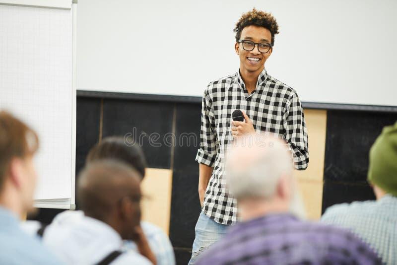 Empresário novo bem sucedido positivo na conferência de negócio imagens de stock