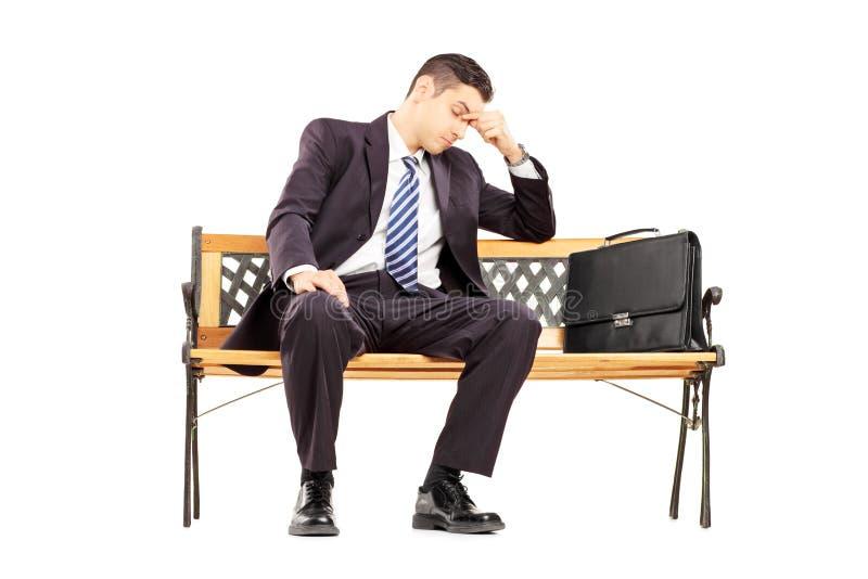 Empresário novo preocupado que senta-se em um banco de madeira imagem de stock royalty free